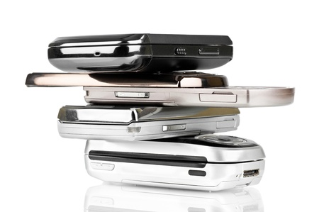 flip phone: Pile of old mobile phones over a white background