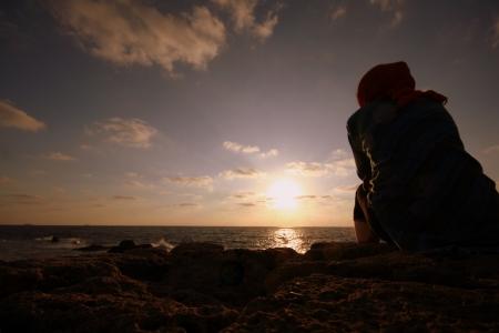 печальный: Девушка, глядя на закат Фото со стока