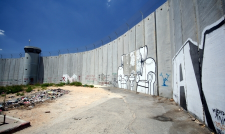 The Israeli separation wall juts into the Palestinian West Bank town of Bethlehem, along the border of Aida Refugee Camp, covered with graffiti by protesters of the barrier  Stock Photo