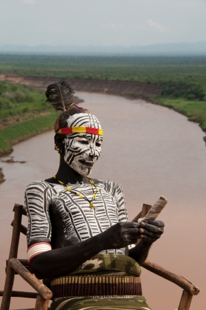 OMO VALLEY-JAN 25 Unidentified Karo Man with village in the background Jan 25, 2012 in Omo Valley, Ethiopia The ethnic groups in the Omo valley could disappear because of Gibe III hydroelectric dam