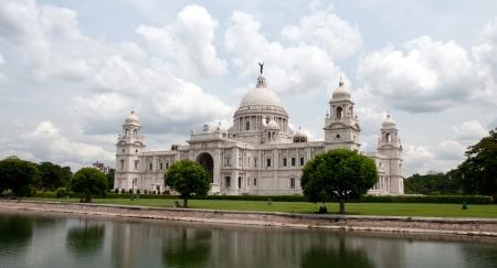 calcutta: Landmark building of Calcutta  aka Kolkata , Victoria Memorial Hall with Queen s Garden in the foreground, pond, white Marble, cloudy sky Stock Photo