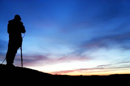 Photographer silhouette in the night sky horizon. Sunset or dawn.