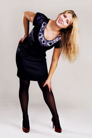 Young cheerful woman in black satin dress on gray background photo