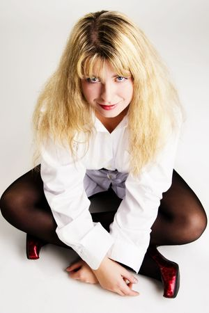 nylon: Lovely playful girl sit on the floor in white shirt on gray background Stock Photo