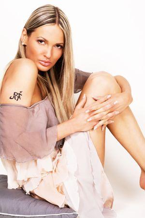Beautiful woman in chiffon dress sitting on a pillow  photo