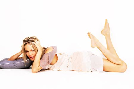 Pretty woman in chiffon dress laying with a pillow photo