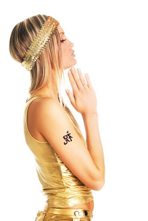 Pretty woman in a prayer pose in golden clothing with tattoo