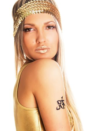 Pretty girl in golden clothing with tattoo on her shoulder