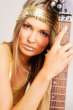 Portrait of a pretty girl with golden make-up holding electric guitar photo