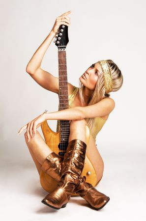 Hübsche Frau in golden Kleidung holding e-Gitarre