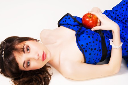 Lovely girl in a bue dress and brilliant diadem with a red apple Stock Photo - 7011235