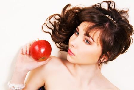 Portrait of a beautiful brunette with red apple photo