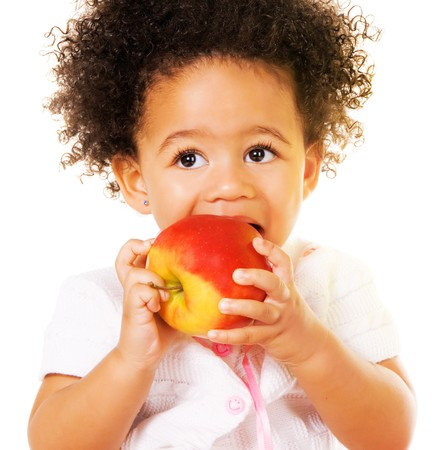 Portrait of a pretty little girl biting an apple Stock Photo