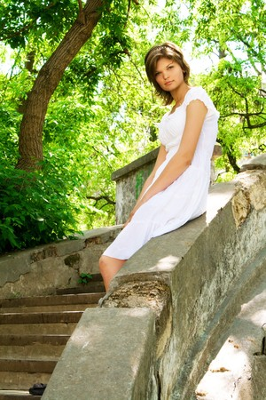 sundress: Lovely young woman in a white sundress outdoors