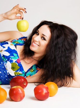 Portrait of a cheerful brunette with fresh fruits on the floor Stock Photo - 7106162