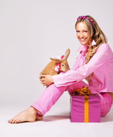 Pretty woman in pink clothing with a rabbit and gift box photo