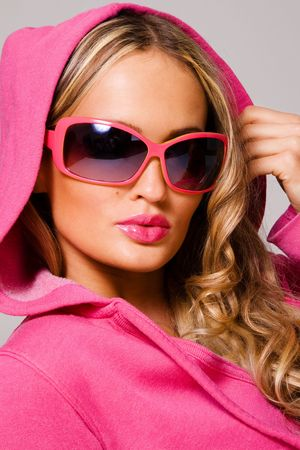 shades of grey: Portrait of a fashionable woman in a pink cowl and sunglasses