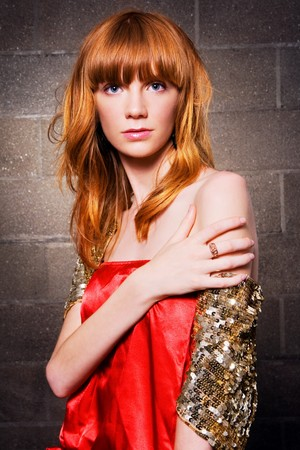 Beautiful red-haired fashion model against brick wall background photo