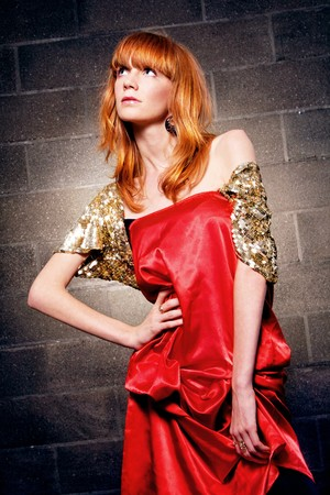 Fashionable red-haired woman in a satin red dress  photo