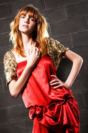Fashionable red-haired woman in a satin red dress against brick wall background  photo