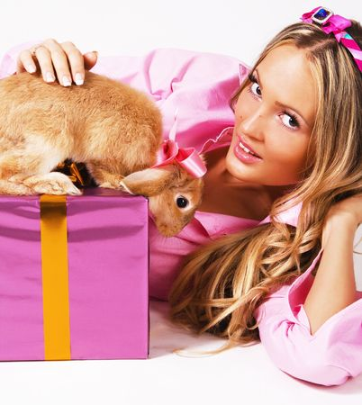 flatter: Pretty woman in pink clothing with a rabbit and gift box Stock Photo