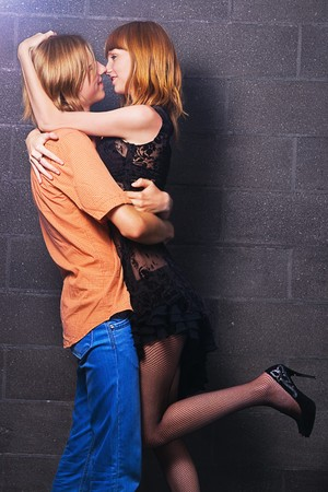 hugging legs: Cheerful young man and woman hug one another against brick wall background