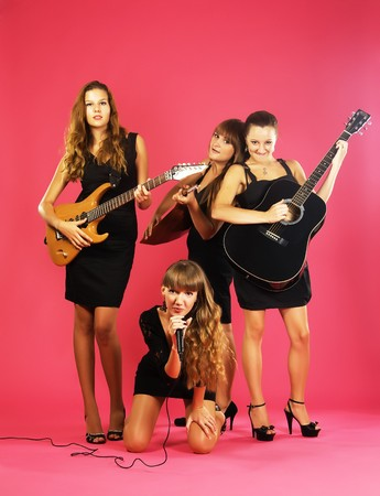 Girls band with musical instruments in elegant black dresses over pink photo