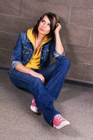 Lovely girl in jean clothing listening a music near brick wall  photo