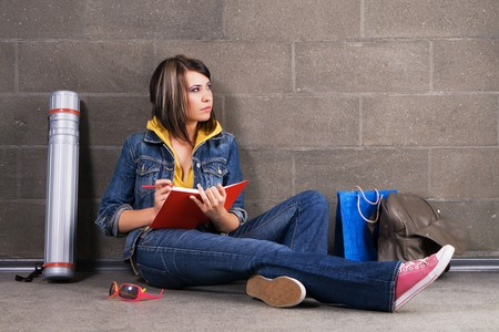 blue grey coat: Pretty student sitting near the wall and writing at notebook