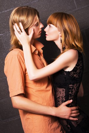 Young man and woman hug one another against brick wall background photo