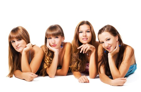 Four lovely girls laying on the floor together. Isolated on white background