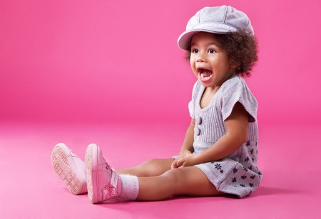 Portrait of a little girl in stylish clothing sitting on pink background and playing up
