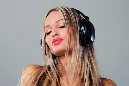 Beautiful girl listening music in big headphones