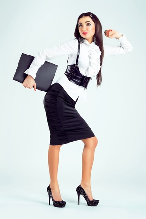 skirt suit: Beautiful stylish businesswoman in motion