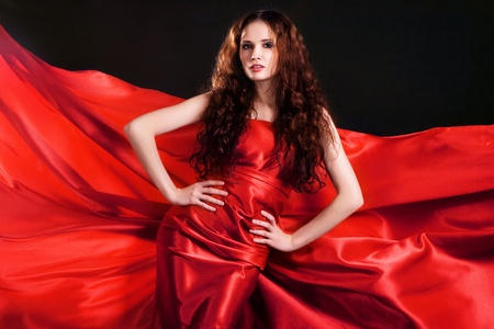 Portrait of gorgeous model in red clothing against black background photo
