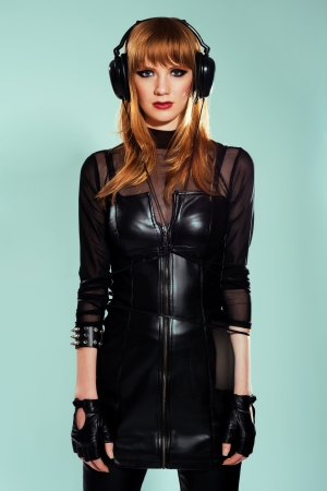 Young beautiful woman in rock style clothing listening music in big headphones  photo