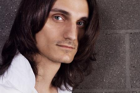 belleza masculina: Closeup retrato de joven guapo en camisa blanca contra ladrillo pared de fondo