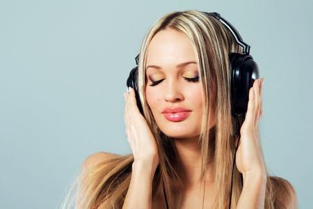 oir: Chica encantadora escuchando m�sica en auriculares  Foto de archivo