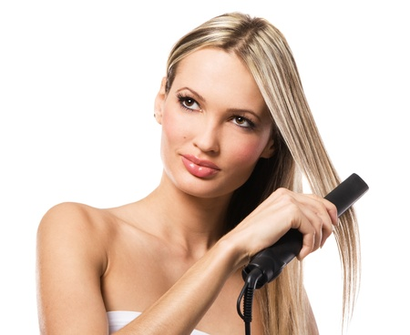 Portrait of young beautiful girl making hairstyle with hair iron photo