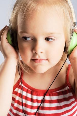 Little girl listening a music in earphones photo
