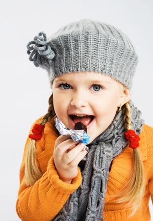 bonbon chocolat: Jolie petite fille mangeant des bonbons de chocolat
