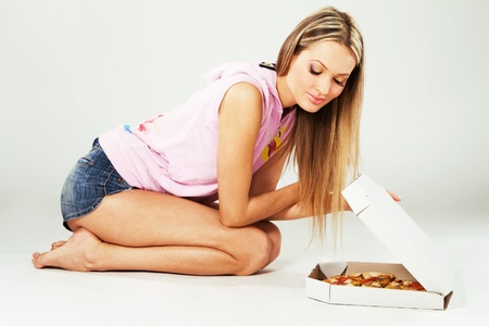 Lovely young woman with whole pizza sitting on a floor photo