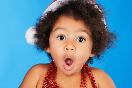 wondered: Surprised little child in Christmas hat against blue background Stock Photo