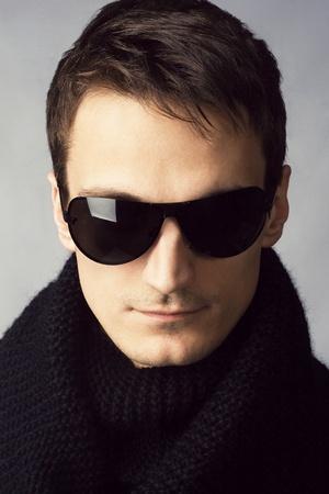 Studio portrait of handsome man in dark sunglasses and black scarf photo