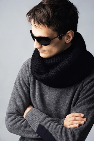 Studio portrait of stylish handsome man in dark sunglasses and black clothing photo