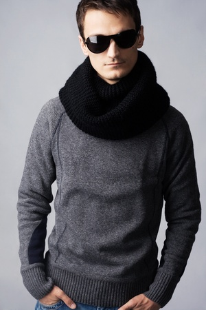 Studio portrait of handsome stylish man in dark sunglasses and black scarf photo