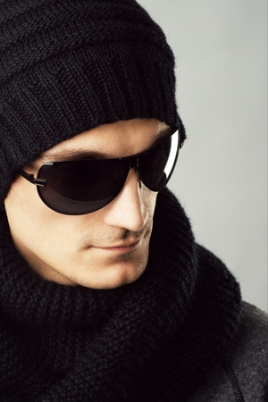 Studio portrait of a stylish handsome man in dark sunglasses and black clothing  photo