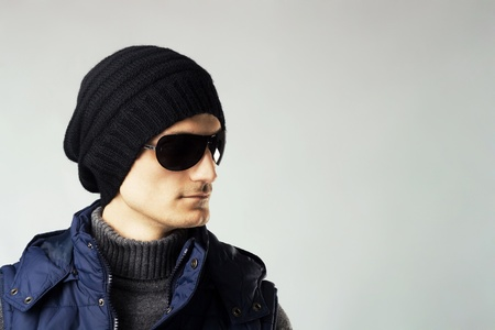 Studio portrait of stylish handsome man in dark sunglasses and down-padded coat photo
