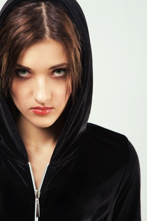 agressive: Portrait of a young angry woman in black hood