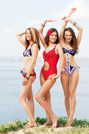 Three young lovely woman having fun on the beach